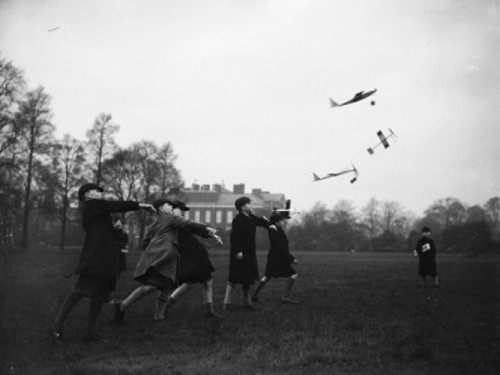 A group of schoolboys hurl their model aeroplanes into flight at Kensington Gardens, London, 1937