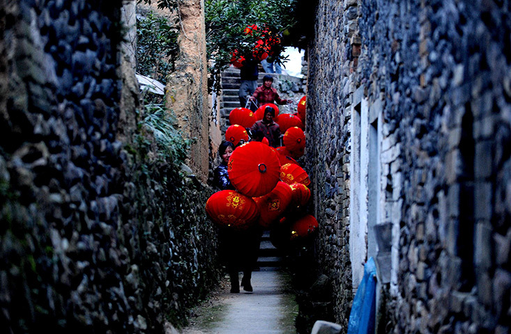 fotojournalismus:  Taizhou, China. Workers carry red lanterns from a workshop. [Credit : AFP/Getty Images]