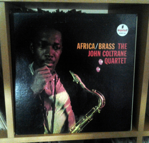 "analog-blog:  John Coltrane - Africa/Brass LP. By NICK DERISO - All About Jazz It's perhaps no surprise that John Coltrane wanted to do something different upon moving to the Impulse label after a long association with Atlantic.No surprise, either, that it might be a recording with a larger aggregate behind him. That was, and is, the style of the day when jazzers seek to get out of the box a bit.Leave it to Coltrane to turn all of that on its ear with ""Africa/Brass,"" a 1961 release that — because of its orchestration — is at once rumbling and mellow, rather than swinging and bright. Coltrane hand picked a back-up group that featured only trumpets, trombones, French horns, tuba and euphoniums (a rarely used baritone horn).Pianist McCoy Tyner, who even then had such burnished layering in his block-style approach, led Coltrane to this place. And it marked the beginning of a period of deep introspection and startling experimentation over the six years that remained before Coltrane's tragic, too-soon passing.Coltrane's only Impulse recording with legendary producer Creed Taylor, ""Africa/Brass"" actually includes, in all but one tune, charts by future Coltrane regular Eric Dolphy — who listened intently to Tyner, and matched his texture and style. These music sheets were created from rough sketches by Coltrane, and workshopped right in the studio.In this way, Coltrane kept the basic quartet approach, despite having all those other guys in the room. The close-knit, absorbing ""Africa/Brass,"" interestingly, had a limited number of solo voices — despite an orchestra that included Dolphy, Booker Little, Paul Chambers, Julian Priester and Freddie Hubbard, among others. It remained immediately identifiable as Coltrane, even in the new setting. We hear an expected, by then, take on a waltz standard in ""Greensleeves"" — something few would question after the artistic and commercial successes of Coltrane's blockbuster ""My Favorite Things"" in 1960. The difference is drummer Elvin Jones, who was becoming ever more confident in the polyrhythms that would dominate jazz in the decade to come.More interesting was the chant-like, almost religious beauty of ""Africa,"" this set's centerpiece — and the launching pad for Coltrane's move away from swing conventions into drones as a compositional foundation. Likewise, ""Blues Minor,"" worked out on the spot by Dolphy in a style that fit well with the stirring creativity now associated with this group, broods and swings with equal power.Just that quick, Coltrane reinvented the one-off, large-group project.Rather than sounding like a patch job, as many of these things so often do, the attention to improvisational detail, and careful selection of instrumentation, instead make ""Africa/Brass"" dark and powerful — adding unexpected hues to one of jazz music's most brilliant improvisers.Unfortunately, this is one of only two big-band sessions by Coltrane (the other being the otherworldly ""Ascension,"" also on Impulse, from 1965). Yet, ""Africa/Brass"" somehow — and this is baffling — remains one of his lesser talked-about releases.To my mind, though, no John Coltrane collection is complete without it. Even four decades later, ""Africa/Brass"" still casts him — and this is saying something — in a new, insistently inventive, light."