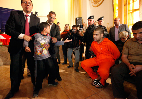 """An Iraqi boy is taken away from a suspected militant who has been accused of killing his father at the height of the sectarian slaughter in 2006-07, during a presentation to the media at the Interior Ministry in Baghdad on November 21, 2011."" (Saad Shalash/Reuters)"
