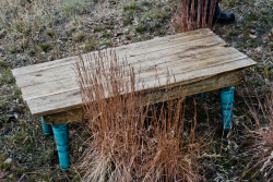 "4′ x 26"" Coffee Table. Crafted from reclaimed wood pallets/deck wood. Hand lathed legs. $200"