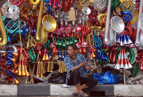edward-appleby:  Jakarta, Indonesia: A vendor waits for customers as he sell paper trumpets for New Year's Eve