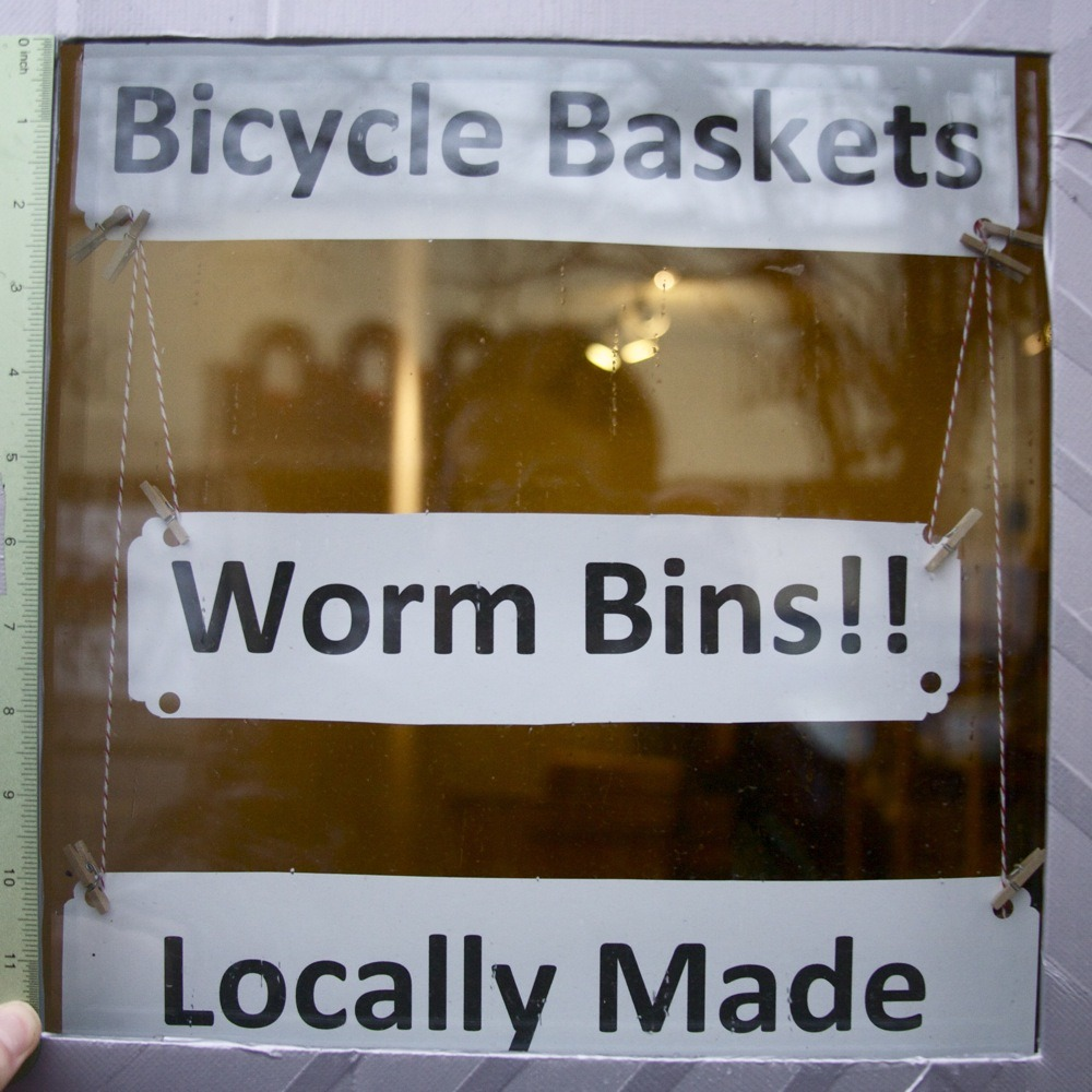 "Storefront window signage, ""BICYCLE BASKETS - WORM BINS!! - LOCALLY MADE"", NE Alberta St. I walked in with worms on the brain and then it smelled awful and for a second I was wondering if OH GOD WORM BINS but that didn't really make a lot of sense, and then I noticed they were painting, and that explained the smell."