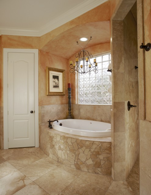 A Tuscan-style master bath with worn faux finished walls, travertine wainscot and Roman steam shower. (via  USI Design & Remodeling)
