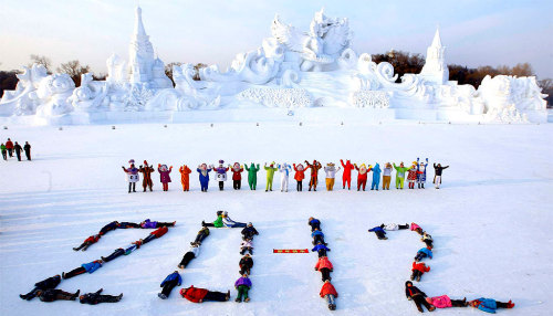 "Children of migrant workers lie on the snow to form the number ""2012″  while celebrating the coming new year in front of a snow sculpture in  Harbin, China. (Associated Press)"