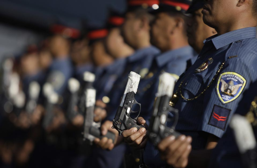 Aaron Favila/AP Photo Filipino police displayed their taped-up pistols at Camp Crame in  suburban Quezon, north of Manila, on Tuesday. The Philippines is working  to thwart the traditional New Year's celebratory gunfire that injures  or kills several people each year.