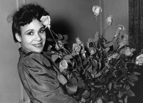 Katherine Dunham with a bouquet of roses, 1940s. Photo via Corbis.