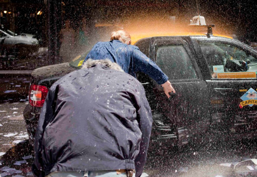 Pablo La Rosa/Reuters People dodged sprays of water as they entered a taxi Friday in the  financial district of Montevideo, Uruguay, where workers throw water at  each other to celebrate the last working day of the year.