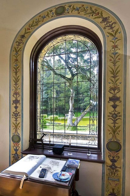 A beautiful arched leaded glass window is surrounded by a colorful frieze fresco painting (via mark pinkerton - vi360 photography)