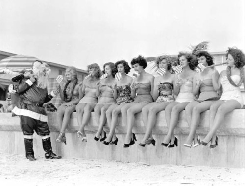 Santa Claus handing out treats to nine young women on the beach: Saint Petersburg, Florida by State Library and Archives of Florida on Flickr.