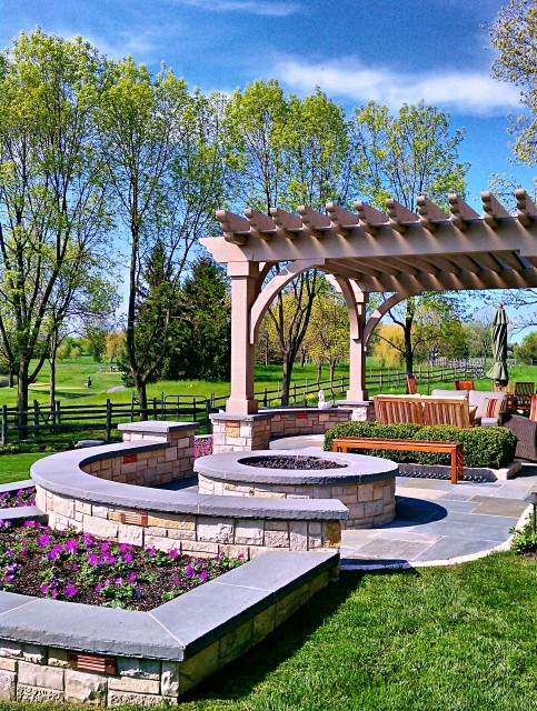 Beautiful backyard landscaping with tiered flower beds and a elegant pergola over a seating area (via Romani Landscape Architecture)