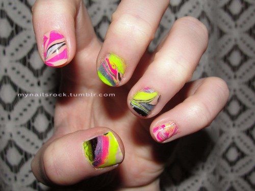 Water marbling with yellow and pink.  Here is some water marbling with neon yellow, pink and some blue glitter splashed around. Polish used: Zoya Avery, Wet N' Wild Black, American Apparel Neon Yellow, Model's Own Blue Moon, & Color Club Warhol