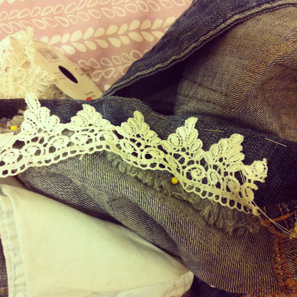 Adding lace, by hand because the sewing machine is broken, to the bottom of some shorts that were a tad bit too short.