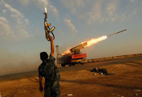 A rebel fighter celebrates as his comrades fire a  rocket barrage toward the positions of government troops on April 14,  2011 west of Ajdabiyah, Libya.  (Chris Hondros/Getty Images)