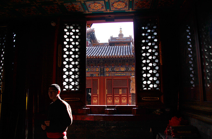 Beijing, China. A monk watches devotees pray at one of the many small temples at the Yonghegong Lama Temple complex. [Credit : David Gray/Reuters]