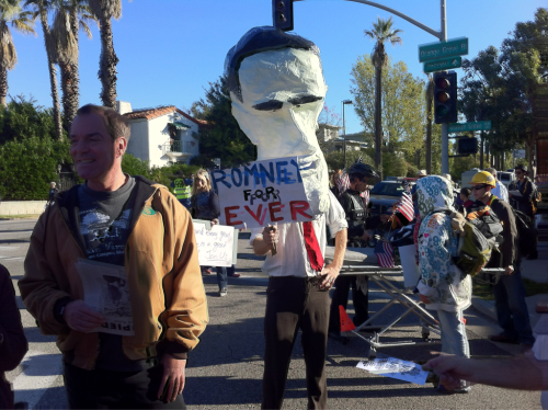 "aheram:  #OTRP - Mitt Romney makes an appearance at Occupy the Rose Parade.  Looks like Jayel Aheram made an appearance at the parade. He has a few shots over at his blog. The L.A. Times, meanwhile, says that the occupiers who showed up got a mixed reaction from the crowd: ""A group of onlookers on an apartment balcony cheered and waved, while some people in the grandstands booed. One man walked past some protesters and said, 'You guys had your 15 minutes.'""  Ouch. Wait, were they looking for 15 minutes?"