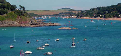 Salcombe Estuary in Salcombe, Devon, on the south western coast of England. The town's extensive waterfront and naturally sheltered harbour has transfigured it into a tourist mecca, especially for the wealthy; since pleasure sailing and yachting are quite popular here. In fact, Salcombe has the second highest property prices in the UK outside of central London.    Wikipedia says there is also a crabbing industry, a statement which leads to rather odd visions in your head, doesn't it? I see a gaggle of old women in sensible shoes and tweeds, grousing about slothful husbands and outrageous prices and moral decline while they methodically lower and rise nets in the water and toss clumps of clicking crabs into a long wooden crate. The crate has sun-faded, peeling boards painted in bright shades of blue.  (takuta on flickr)