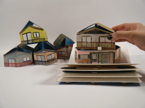 "Mix and Match Your Own Vancouver Special, a mixed media handmade pop-up book designed, illustrated, and constructed by Priscilla Yu, 2009. Priscilla writes:  The book showcases Vancouver's most loathed boxy homes, characterized by its seeming love of stucco, Italian imported wooden front doors, and cookie-cutter design. Rethinking and embracing it's aesthetic, in a whimsical way, the seven-paged book is an interactive experience, where the reader can play builder in selecting a series of ""tops"" and ""bottoms"" to create their very own Vancouver Special homes.Priscilla Yu is a fourth year illustration student at Emily Carr University. She lives in and was raised in a surburb within Vancouver, and loves anything to do with houses.  More images here, along with video. Thanks for the submission, Priscilla!"