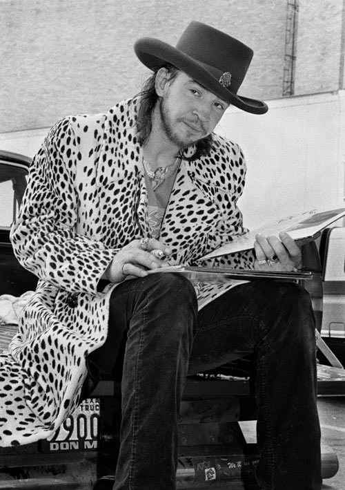 "Stevie Ray Vaughan signing bootlegs Stevie signs his own bootlegs in 1986 (""asking me why!"" notes photographer Tracy Anne Hart) outside Sam Houston Coliseum."