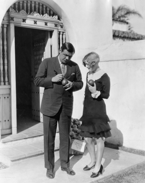 Actress Marion Davies helps baseball great Babe Ruth autograph oranges during a visit to Southern California - 1927
