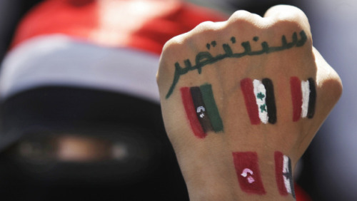 "A Yemeni female protestor shows her hand with Arabic that reads, ""We  will prevail,"" and the colors of pre-Qaddafi Libya, Syria, Yemen,  Tunisia and Egypt, during a demonstration demanding the resignation of  Yemeni President Ali Abdullah Saleh in Sanaa, Yemen, Wednesday, Oct. 26,  2011. (AP Photo/Hani Mohammed)"