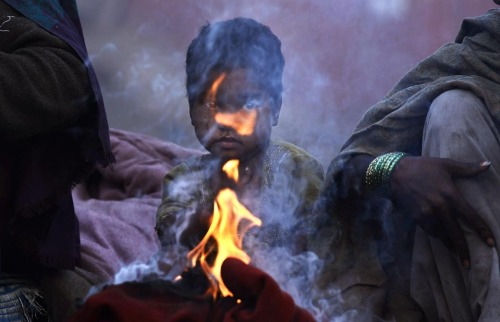 fotojournalismus:  A child sat near a fire on a cold morning in New Delhi, Tuesday, Jan. 3, 2012. [Credit : Adnan Abidi/Reuters]