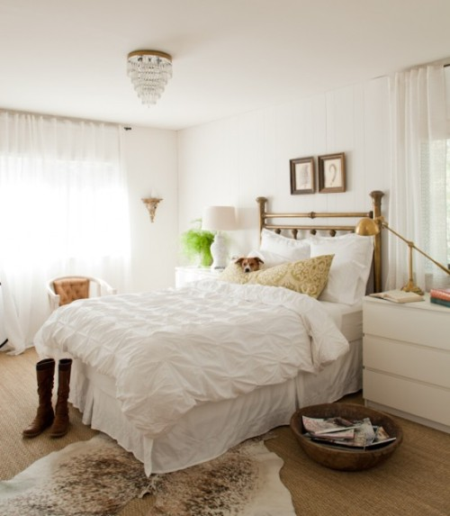 A classic and elegant bedroom done in white, with neutral accents and a delectable vintage brass headboard… plus I love the dog peeking over the pillows. (ok, that's not part of the decor, it's just cute!) (via Lauren Liess Interiors)