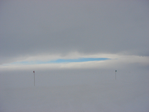 "Blind in Antarctica    Audrey M Yau | Dept. of Geosciences  This photograph was taken in the middle of a rough snowstorm in a field near McMurdo Station, Antarctica. With low visibility and strong winds whipping words out of earshot, a colored flag is the only guide on the Antarctic ice. Red and green indicates ""okay to pass""; black indicates a crevasse. Out here, life depends on simple, critical designs.   (source)"