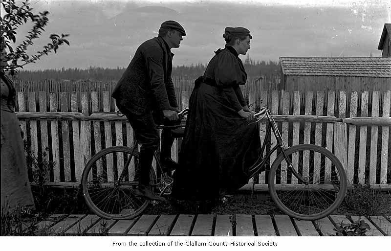 "afrormosia:  ""Man and woman on a tandem bicycle, probably on the Olympic Peninsula."" (University of Washington Digital Collections, Clallam County Historical Society Digital Collection, 59.46.6.)"