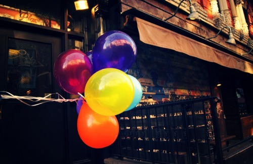 "St. Mark's Place party balloons. East Village, New York City.  Before I run off to do birthday things, since today is my birthday (yes!), I wanted to share this lovely festive photo of balloons blowing in the wind on St. Mark's Place in the East Village along with some information about how to find me on Google Currents.   It turns out that I am now a curator on Google Currents and this means that you can now view my photos and posts on your Android, iPhone and iPad. I really love the layout and how feeds look on Google Currents. I hope you do too. You can find me there by clicking here:   Vivienne Gucwa's New York City photography on Google Currents  I have been having a really wonderful birthday week. I will post more about the new lens I received as an early birthday gift on Monday in another post. Suffice to say that I am having a blast and there are cupcakes on my current agenda. How can you go wrong with that?!   —-  View this photo larger and on black on my Google Plus page  —-  Buy ""Balloons - East Village - New York City"" Posters and Prints here, View my store, email me, or ask for help."