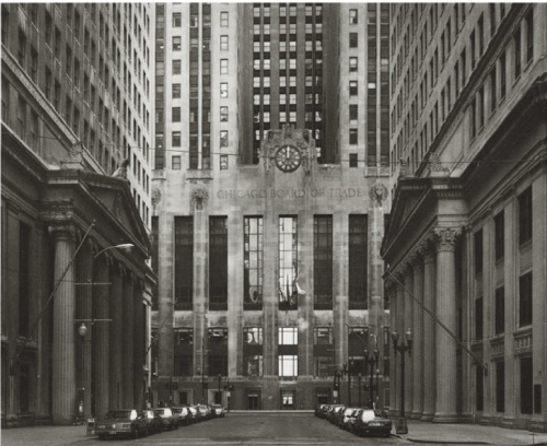 "If we look at an image titled South LaSalle Street (Chicago Board of Trade), Chicago 1992, by the German photographer Thomas Struth, we see what appears to be a typical form from the artist's opus. Positioned in the dead center of the street, a vantage point the artist took for a vast series of street scenes made over several decades, we see two structures with pillared facades adjacent to each other, both guarded by a row of parked cars. Framed by these two buildings, the Chicago Board of Trade sits paramount in the center of the street. There is not a soul in sight, yet beyond the walls of this edifice, open outcry trading takes place, thus shaping the rise and fall of our world markets. In fact, established in 1848, the Chicago Board of Trade is the world's oldest futures and options exchange. As your eyes navigate through the black & white picture everything is doubled, as though one half of the image is looking into a mirror. Even the light spills with a soft equity and the faint shadows casted on the twin buildings guide your eyes to the highlighted glass windows in the middle, which leads invariably to the picture's centerpiece, the clock.     In the opening pages of Austerlitz, by W.G. Sebald, we find ourselves in Antwerp Central Station looking up at the ""mighty clock, the dominating feature of the buffet,"" which not only oversees all of the comings and goings of travellers, but also ""reigns supreme"" above a grand display of symbolic imagery and exquisitely detailed architecture. The protagonist, Austerlitz, observes that even in a splendid station such as this, with so much to take in, like the enormous dome meant to evoke the Pantheon in Rome, the station itself ""a cathedral consecrated to international traffic and trade,"" it is the clock that sits above the ""only baroque element in the entire ensemble,"" thus governing the space and activities of all those within it. The clock torments the two characters in Sebald's novel as they sit in the restaurant near the station's waiting room: During the pauses in our conversation we both noticed what anendless length of time went by before another minute had passed,and how alarming seemed the movement of that hand, which resembled a sword of justice, even though we were expecting it every time it jerked forward, slicing off the next one-­‐sixtieth of an hour from the future and coming to a halt with such a menacing quiver that one's heart almost stopped. (p 8)         One may have the exact same response when discovering that the hands on the clock in Struth's photograph rest precisely at twelve o'clock on the dot, at once becoming another perfect line in unison with the others in the picture, which brings the viewer to a halt when realizing how Time also reigns supreme throughout Struth's work. While the freezing of time is the very nature of photography itself, Struth has doubly stopped time, not only by making the picture when the clock struck twelve, but by what he has pointed the camera at throughout his life as a photographer; symbolic structures of commerce, politics, religion, and bastions of art, which span the centuries and the globe in an attempt to apprehend the past and future. Likewise, Sebald brings to mind the structure of the Antwerp railway station as Austerlitz explains to the narrator how the architect of the station, Delacenserie, was ""uniting past and future"" by basing the station on the Pantheon in Rome. While Sebald uses the observations and historical knowledge of his character on the structures surrounding him in order to conjure up the clash of the past and present, Struth achieves this by sequencing his photographs, not by their original project oriented context, but by his own conceptual design, so that when we turn the page in his retrospective book Thomas Struth 1977-­‐2002, to the picture preceding South LaSalle Street (Chicago Board of Trade), Chicago 1992, with its ominous clock forever fixed in time, we are confronted by the large-­‐scale color photograph Pantheon, Rome 1990. By bringing to mind the Pantheon both Struth and Sebald have gone as far back as possible in the history of symbolic architecture to face us with the past."