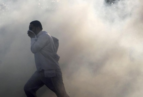 fotojournalismus:  A man ran as tear gas enveloped Sitra, Bahrain, Wednesday, Jan. 4, 2012. Clashes between antigovernment protesters and police erupted during a procession marking the third day of mourning for a teenage boy who was killed during earlier clashes. [Credit : Hasan Jamali/Associated Press]