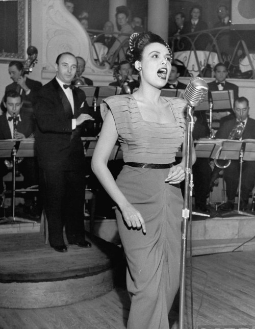legrandcirque:  Lena Horne singing into a mike on stage as the bandleader conducts an orchestra behind her in a nightclub. Photograph by Yale Joel. Paris, December 1947.