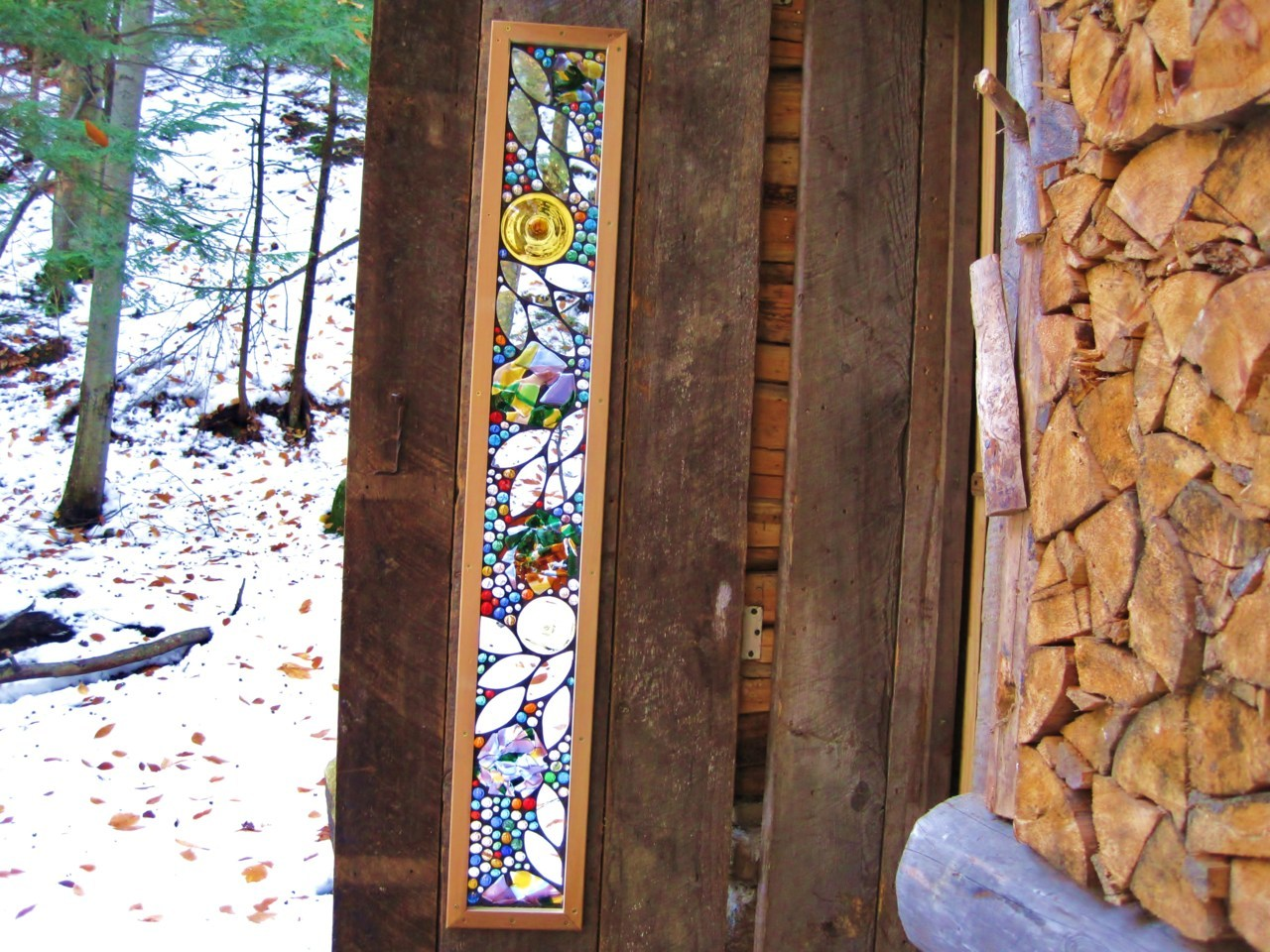Door installation in a quaint Cordwood cabin.. This piece has slumped glass in it. The outside is protected with plexiglass, and installed with a space between the stained glass and plexiglass to make it a double paned window.
