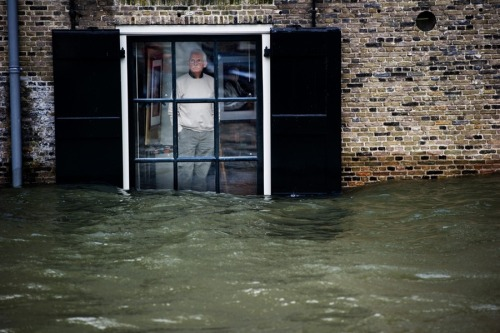 fotojournalismus:   A Dutch local resident watches floodwaters through his window, in Dordrecht on Jan. 5. Gale force winds and heavy rains are expected along the Dutch coast. About a quarter of the country sits below sea level. [Credit : Robin Utrecht / AFP / Getty Images]