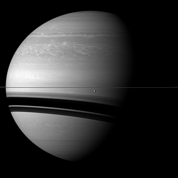 The immensity of Saturn Saturn's moon Tethys orbits in front of the wide shadows cast by the rings onto the planet for this Cassini view.Tethys (660 miles, 1062 kilometers across) appears just below the rings near the center of the image. This view looks toward the northern, sunlit side of the rings from less than one degree above the ring plane.The image was taken with the Cassini spacecraft wide-angle camera on Dec. 7, 2011 using a spectral filter sensitive to wavelengths of near-infrared light centered at 752 nanometers. The view was obtained at a distance of approximately 1.1 million miles (1.8 million kilometers) from Tethys. Image scale is 66 miles (107 kilometers) per pixel on Tethys.  via the-star-stuff