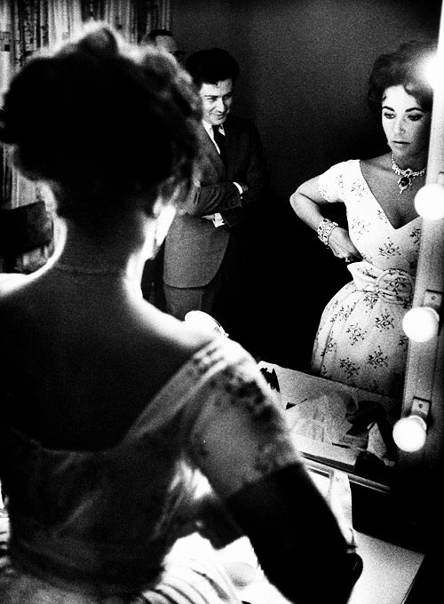 Eddie Fisher admiring Elizabeth Taylor as she primps in front of the mirror in his dressing room, before his show, photographed by John Bryson, 1959.