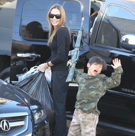 Angelina Jolie was recently spotted toy gun shopping with her two sons, Maddox (not shown) and Pax in Hollywood, following a quick lunch at McDonald's. Jolie, a U.N. ambassador and peace activist, was all smiles while Pax appeared to pretend to be hit with bullets while holding a large toy machine gun. The photo comes just two days after a Texas eighth-grader was shot by police for brandishing a pellet gun at school. What do you think of Angelina's choice to let her sons play with toy guns in public? Is it a case of boys being boys, or does the Oscar-winning mom need to rethink her decision to allow it? Tell us in the comments below. CLICK HERE FOR MORE ANGELINA JOLIE PHOTOS FROM X17 ONLINE. (Photo courtesy of X17 Online)