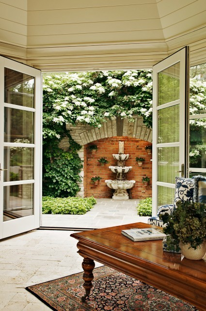 Glass French doors open onto a walled terrace garden, which features a tiered fountain inside a niche (via Will Waibel)