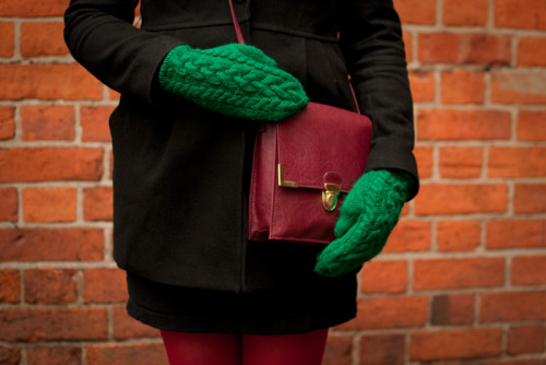 green cable mittens worn by a happy customer.