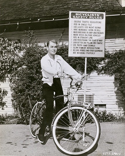 Alan Ladd rides a bike. And obeys the rules.