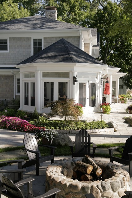 An octagonal screened porch, with limestone tile floors, adorns this pretty cedar shake sided home (via Martin Bros. Contracting, Inc.)