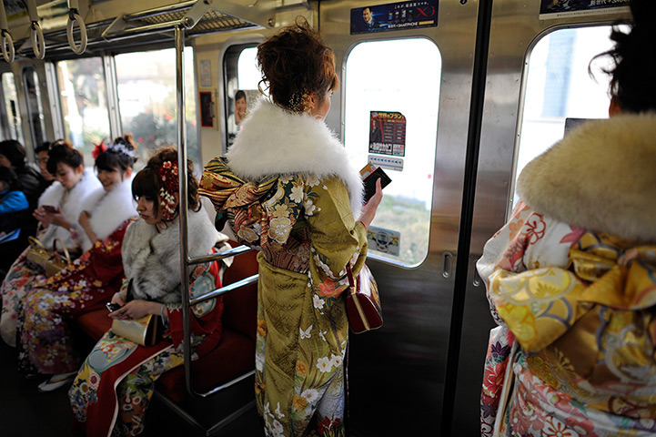 Tokyo, Japan. Kimono-clad 20-year-old Japanese women on a train after attending a ceremony marking the Coming of Age Day at the Toshimaen Amusement Park. [Credit : Franck Robichon/EPA]