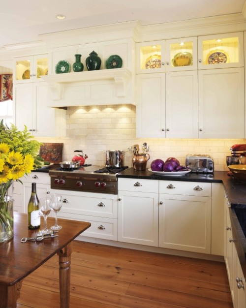 This bright and pretty kitchen uses upper glass-fronted cabinets as lighted display spaces (via Venegas and Company)