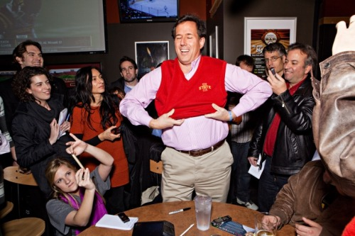 "In Iowa last week, Rick Santorum tries on a sweater vest (what else?) surrounded by a ring of reporters, wearing an expression that was described to us as ""a complete look of ecstasy."" Our Alex Altman is the skeptical one in the back left of the frame.  Photo by Lars Tunbjork for TIME"