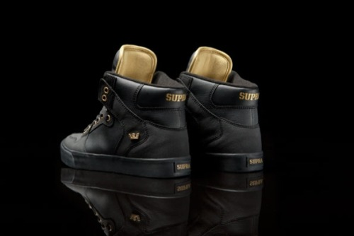 "SUPRA VAIDER ""MLK"" The Supra Vaider is a dope silhouette that is capable of setting off a much wider array of outfits than many casual streetwear sneakers. With a hot black on black colorway, the ""MLK"" Vaider features Supra's iconic TUF upper with gold details in the eyelets, branding and backs of the tongues. The colorway signifies Martin Luther King, Jr.'s dream-formulating days at Cornell, with the colors of his fraternity at Alpha Phi Alpha. Available now wherever Supras are sold."