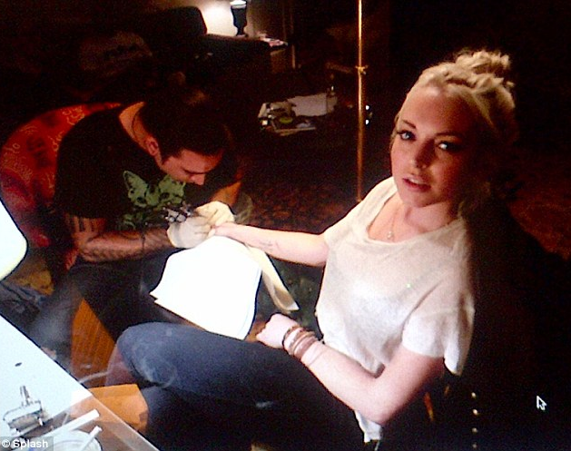 Here's Lindsay Lohan getting tattooed in what seems to be a house. How hygenic. ^ Here's a picture of the tattoo, hopefully the image works. If not, the tattoo says 'live without regrets', and it looks pretty terrible. I'm sure she'll live to regret this tattoo.