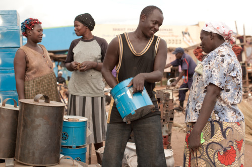 Suda Okello, a store owner who sells stoves to his community at an affordable price, explains the health and income benefits of charcoal-efficient stoves to a customer. Learn more at www.theadventureproject.org. Photo by Esther Havens.