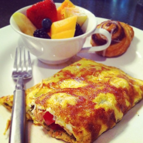 sarahsamudre:  Breakfast: Salmon, Brie & Grape Tomato Omelette (Taken with instagram)  Four Eggs 1 tsp Milk 1 tsp Olive Oil 1/2 cup Grape Tomatoes Triple Creme Brie (also good: another triple creme, Delice de Bourgogne) Baked Salmon (5-6 ounce fillet of salmon, 1/4 onion, 3 slices apple, one clove garlic, salt and pepper. Preheat oven to 400F, place salmon on sheet of parchment paper. Place apples, onions, garlic and seasoning on top of salmon and twist up parchment paper. Bake for 15 minutes. Set aside for at least ten minutes before removing from skin, cutting into pieces and adding to omelette. Only use half and save the rest to top a midday salad.) Mix until the eggs, olive oil and milk create a nice frothy mixture. Preheat your pan on medium heat for at least five minutes before adding the omelette. Grease your pan with your grease of choice (I use an organic cooking spray instead of butter). Once you've poured your egg mixture in, swirl it around so it evenly coats all sides of the pan. Keep doing this every 15 seconds until the omelette begins to firm up. As it cooks, sprinkle with fresh dill, if you have some. Dried works just as well. Take triple creme brie, distribute down center of the omelette. Add freshly baked salmon and sliced grape tomatoes on top of the melting brie. Fold omelette in thirds, flip and either serve whole to one VERY hungry person, or cut in half while still on the pan, as I did. Leave it on the pan once it's been halved for an extra 30 seconds. Then serve.   I've been without coffee this year and this is the first morning I've felt this much energy since giving it up. It must be the salmon!