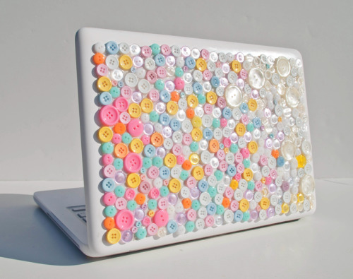 The Boutique Button Stickybun laptop skin from Rapt!  Starting at $32.50 The Boutique Button StickyBun is a 3-Dimensional look that is much more visually exciting than a skin but still maintains a thin, lightweight protective cover that is applied directly to a laptop. This button StickyBun was designed to be transparent so that the laptop color will still be seen giving the illusion that the buttons are applied right to your laptop. This StickyBun is a specialty item because of all the small eclectic buttons that fade from one corner to the other. Notice the high gloss of the buttons and pretty pastel of the colors that make this item so fun and playful! On the back there are thin strips of clear adhesive along the edges and adhesive dots in the middle. The adhesive stays very well, but can be taken off at any point. The StickyBun can be removed by simply peeling off the StickyBun and rolling off any leftover gel with your fingertips. The Boutique Button StickyBun is extremely durable. It protects laptops from nicks and scratches while looking fun and unique. Because the items are handmade in the United States, the arrangement of the buttons will not be the same as they appear in the photos but the concepts, creativity, and care will remain the same.  Click on the photo to be directed to the Rapt website for purchase or more info! Follow us on twitter for the latest news and special deals! @All_Rapt_Up